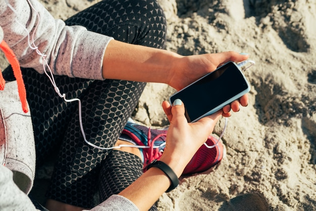 Girl in sportswear listening to music in headphones on a mobile phone on the beach in the morning Premium Photo