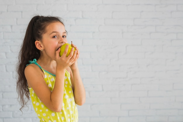 Girl standing in front of wall eating green apple Free Photo
