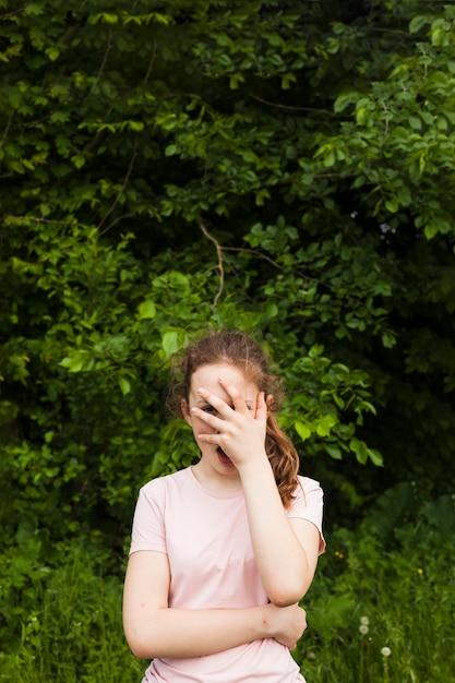 Girl standing in park peeking through her finger Free Photo