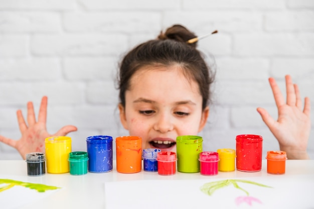 Girl standing behind the table looking at colorful paint bottles Free Photo