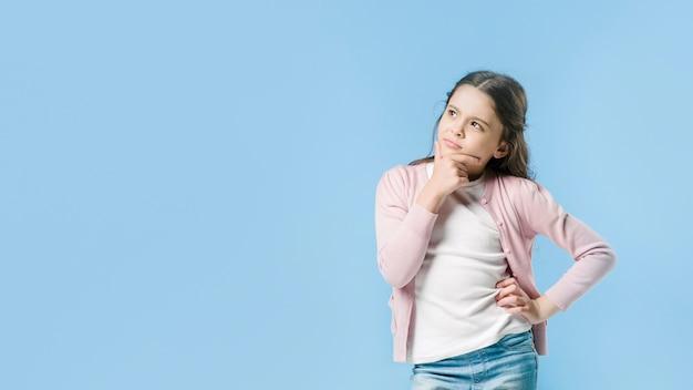 Girl standing and thinking in studio Premium Photo