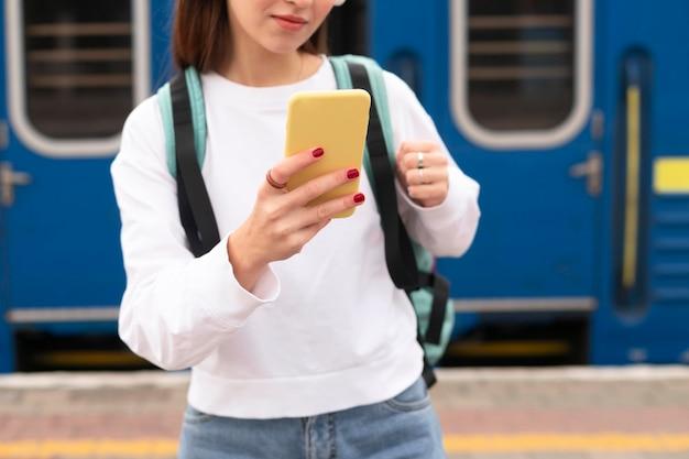 Ragazza in piedi accanto al colpo medio del treno Foto Gratuite