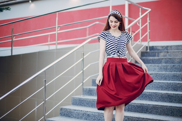 Girl in a stands holding her red skirt Free Photo