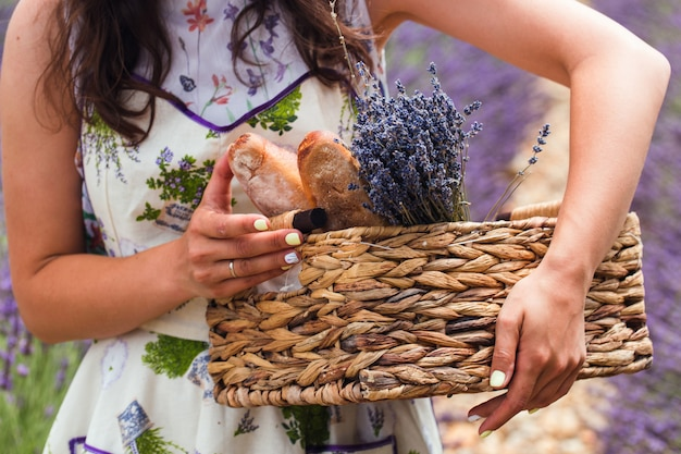 A girl stands in the middle of a lavender field, holding in her hands a basket Premium Photo