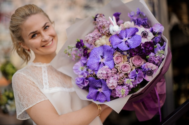 Girl stands with a completely purple bouquet Premium Photo