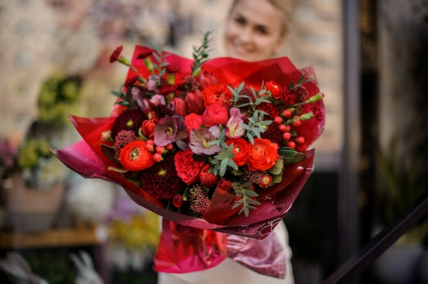 Girl stands with a completely red bouquet Premium Photo