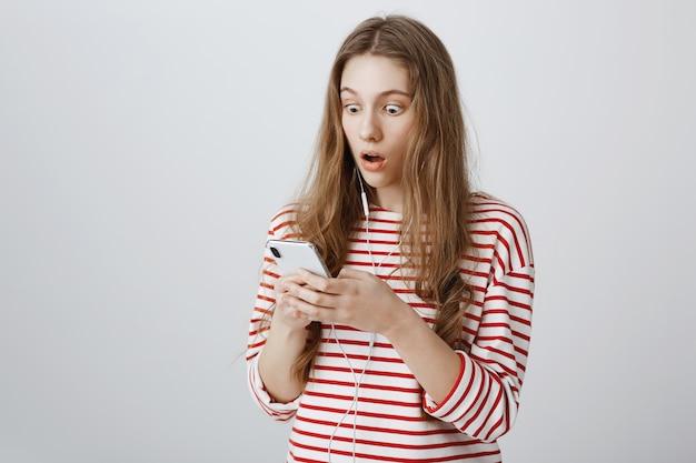 La ragazza fissa il cellulare sorpresa, leggendo notizie scioccanti Foto Gratuite