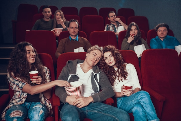 Girl steals popcorn from box of couple in love. Premium Photo