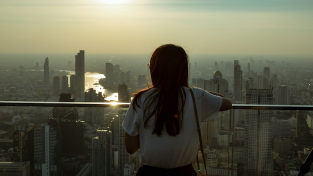 Girl stood on the roof of the building looking at the city full of dust and air pollution Premium Photo