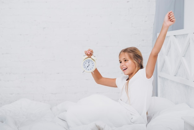 Girl stretching while holding a clock Free Photo