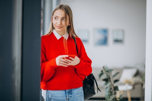 Girl student in red sweater using phone Free Photo