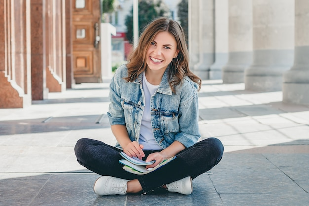 Girl student sits opposite the university and smiling. cute girl student holds pensil, folders, notebooks and laughs. girl teaches lessons Premium Photo