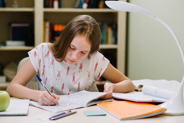 Girl student sitting and writing Free Photo