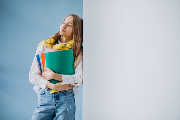 Girl student standing with colorful folders Free Photo