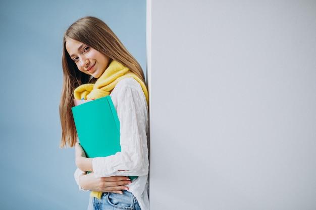 Studentessa che sta con le cartelle variopinte Foto Gratuite