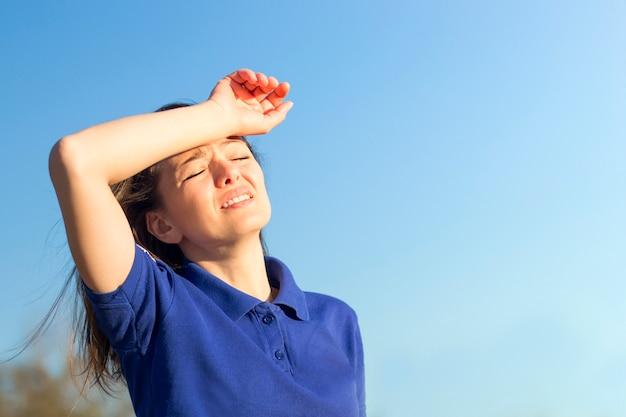 熱中症の痛み、熱、女性に苦しんでいる女の子。夏の暑さで日射病を患っています。危険な太陽、日光の下の女の子。頭痛、気分が悪い。人は頭に手を握る。 Premium写真