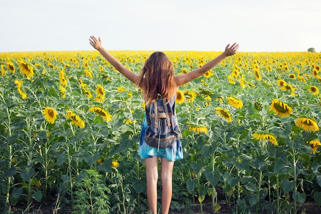 Girl in sunflower field, an emotional girl, a young girl goes into a field of sunflowers, seen from behind; copy space Premium Photo