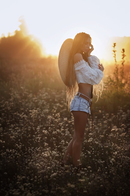 Girl at sunset in a hat. field of white flowers. dreadlocks. beautiful summer look Premium Photo