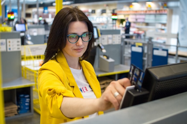 Girl in the supermarket to check their own reading of the customer card Premium Photo