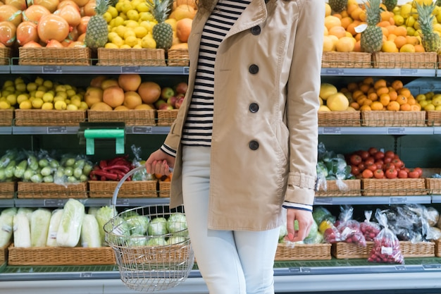 Girl in the supermarket chooses vegetables and fruits Premium Photo