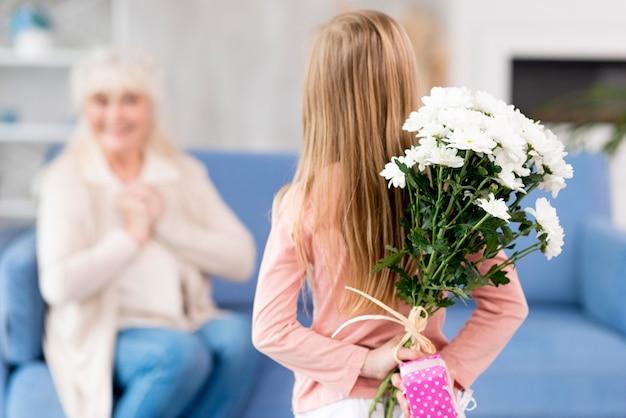 Girl surprising grandma with flowers Premium Photo
