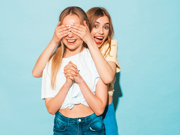 Girl surprising her female best friend. model covering her eyes and hugging  from behind. Free Photo