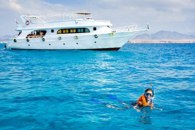 青い海で泳いでいる少女 Premium写真