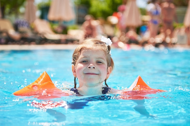 夏の暑い日に腕輪のプールで泳いでいる少女。トロピカルリゾートでの家族での休暇 無料写真