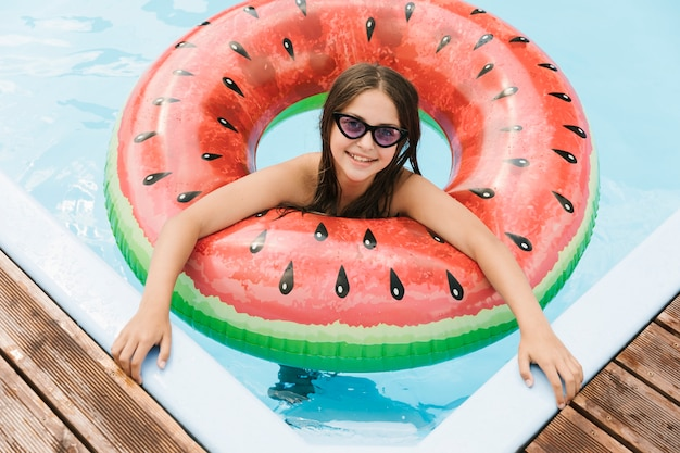Girl in swimming pool with watermelon floatie Free Photo