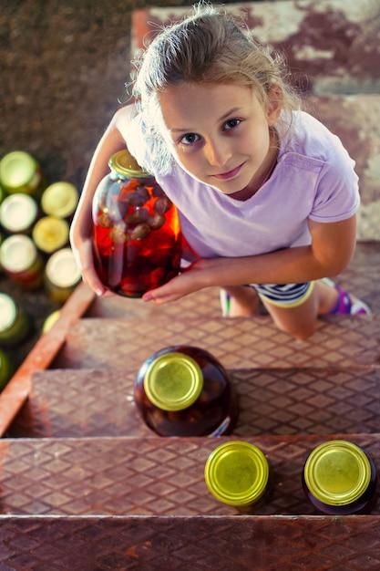 Девушка берет из погреба большие стеклянные банки с домашним клубничным компотом Premium Фотографии