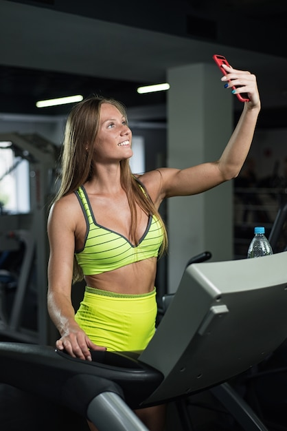 Girl takes a selfie in the gym, woman is photographed on the treadmill Premium Photo