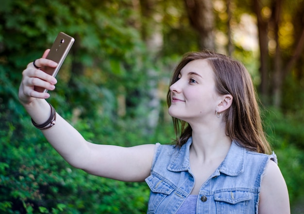 The girl takes a selfie on the phone. Premium Photo