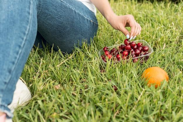Girl taking cherries sitting on the grass Free Photo