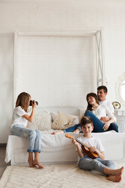 Girl taking photo of her parents and her brother playing ukulele at home Free Photo