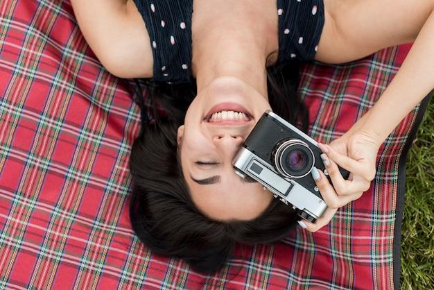 Girl taking a photo on picnic blanket Free Photo