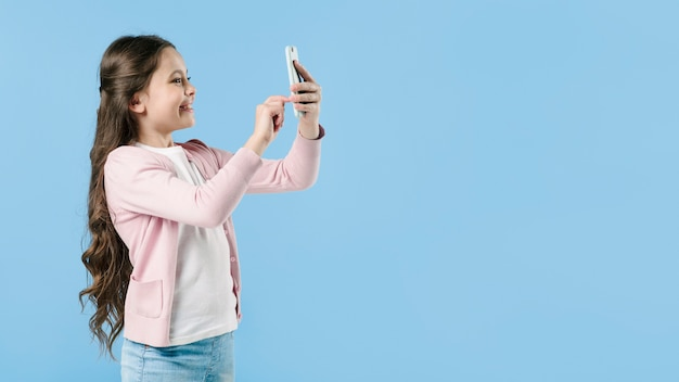 Girl taking picture with phone in studio Free Photo