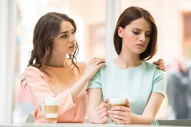 Girl talking with her upset friend and holding her shoulders Premium Photo