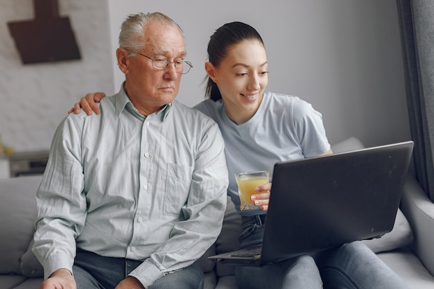 Girl teaching her grandfather how to use a laptop Free Photo