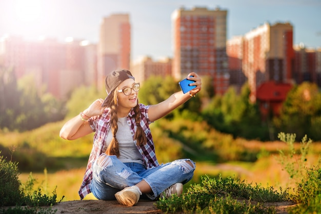Girl teenager in glasses sits the ground city background Premium Photo