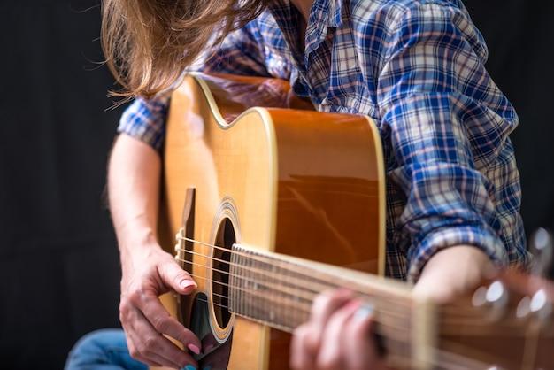 スタジオで暗い背景にアコースティックギターを弾く少女10代。コンサートの若いミュージシャン Premium写真