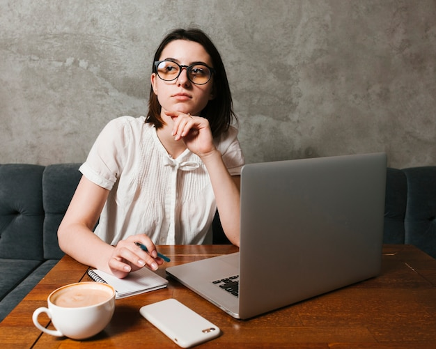 Girl thinking in front of laptop Free Photo