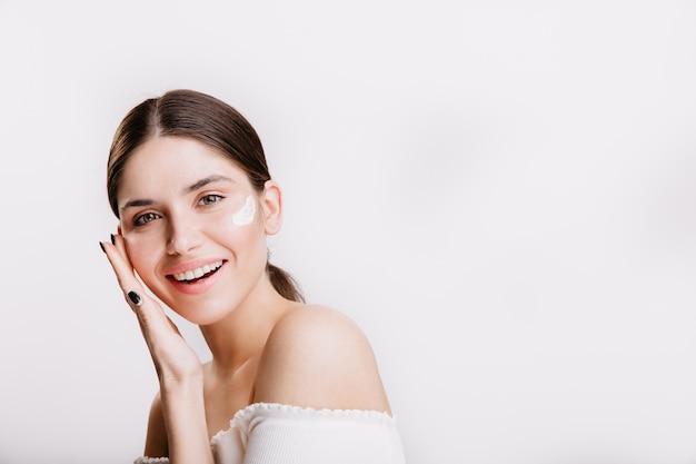 Девушка трогает увлажненную кожу и улыбается. портрет модели с кремом на лице на изолированной стене. Бесплатные Фотографии