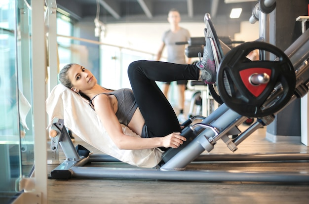 Girl training her legs with a machine in the gym Premium Photo