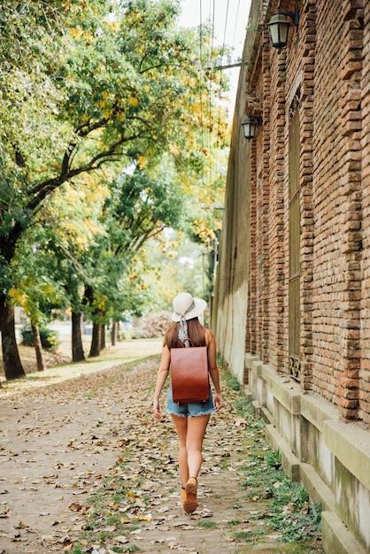 Girl traveler carrying her backpack Free Photo