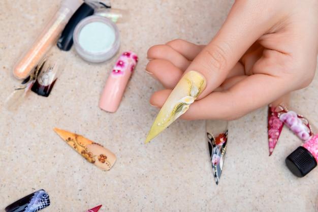 Девушка примеряет искусственные ногти с цветочным дизайном ногтей Бесплатные Фотографии