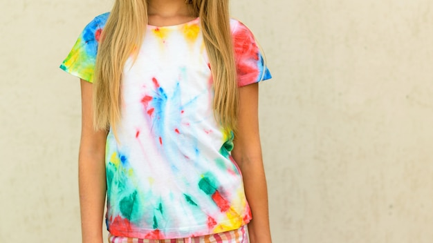 Girl trying on a t-shirt painted in the style of tie dye. Premium Photo