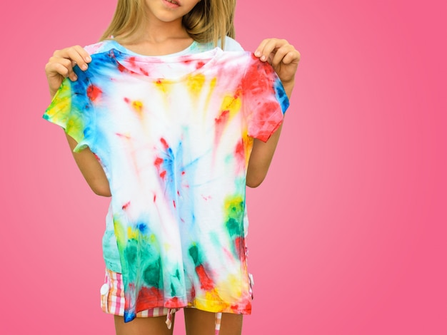Girl trying on a t-shirt in the style of tie dye on a red wall. Premium Photo
