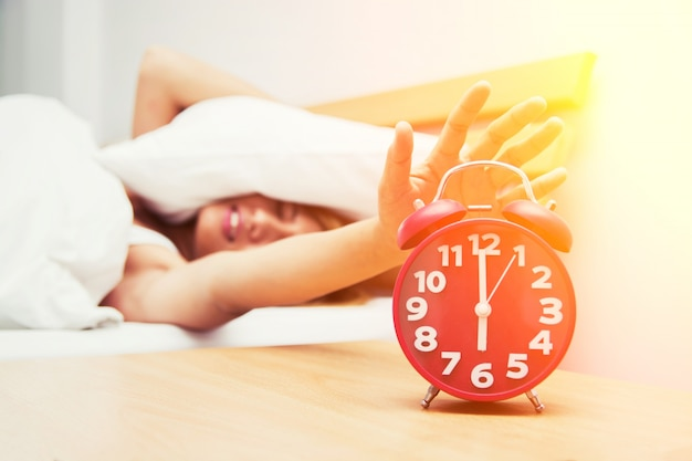 Girl turning off the alarm clock Free Photo