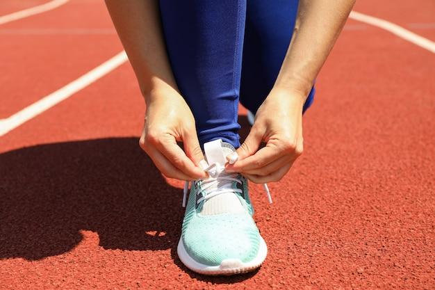 Девушка, связывая шнурки на красной спортивной беговой дорожке, крупным планом Premium Фотографии
