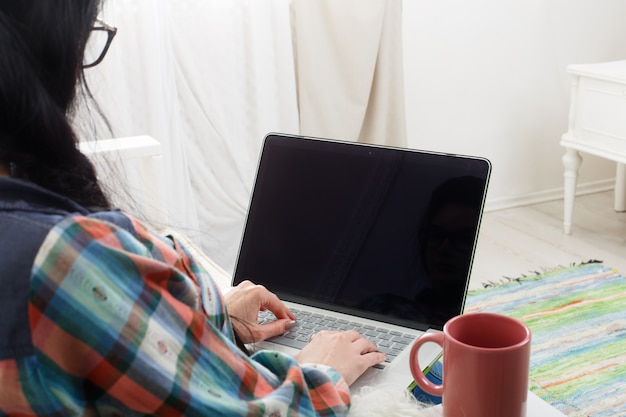 Girl typing on laptop with copyspace at screen Premium Photo